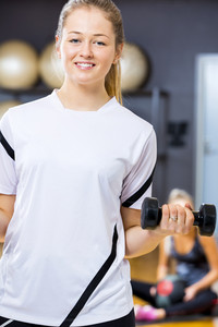 Smiling woman in workout outfit holds dumbbell at fitness gym