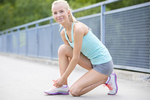 Smiling woman runner tying shoelaces on bridge