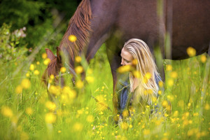 Smiling woman sits in the meadow with her arabian horse