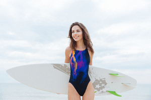 Smiling woman surfer in swimwear standing and holding surfboard on the beach and looking away
