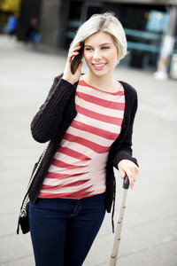 Smiling Woman Talking On Smart Phone Outside Railroad Station