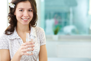 Smiling woman with a glass of water looking at camera