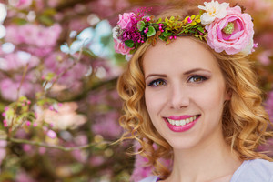 Smiling woman with blond hair with flower wreath against pink tree in blossoom, spring nature