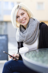 Smiling woman with coffee and using phone outdoor