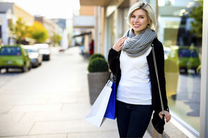 Smiling Woman With Purse And Shopping Bags Outside Store