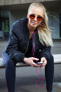 Smiling woman with sunglasses sits outdoor and uses phone