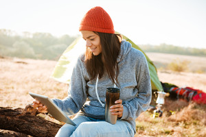 Smiling woman with tablet near the tent