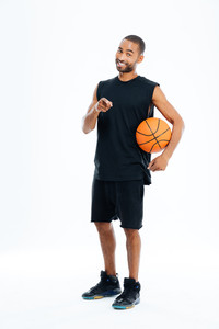 Smiling young african sportsman holding basket ball and pointing finger at camera isolated on a gray background