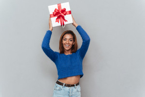Smiling young african woman in sweater and jeans holding gift overhead and looking at camera. Isolated gray background