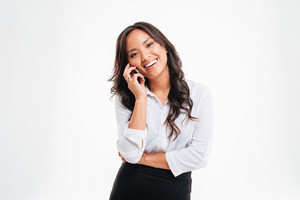 Smiling young asian businesswoman talking on the phone isolated on a white background