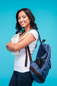Smiling young asian student girl standing with books and backpack isolated on a blue background