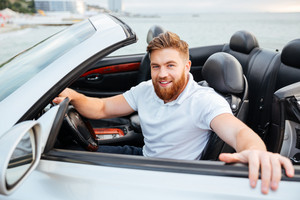 Smiling young bearded man getting out of his car