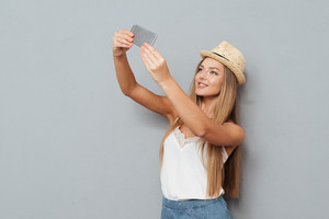 Smiling young beautiful girl in hat making selfie photo on smartphone over gray background