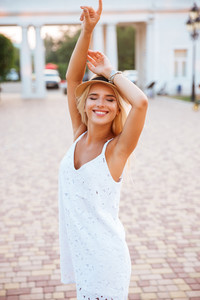 Smiling young blond girl posing with her hands up outside at the park