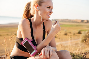 Smiling young blonde fitness woman resting and listening music with earphones and smartphone outdoors