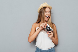 Smiling young blonde girl in hat holding photo camera isolated on a gray background
