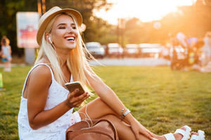 Smiling young blonde woman listening to music while sitting on grass in park
