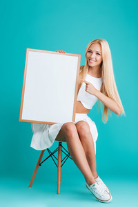 Smiling young blonde woman pointing finger at blank board while sitting on chair isolated on the blue background