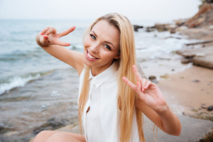 Smiling young blonde woman showing v sign at rocky beach on a sunny day