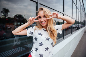 Smiling young blonde woman showing v sign while standing outdoors at the glass building