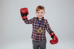 Smiling Young boy in boxing gloves looking at camera. Isolated gray background