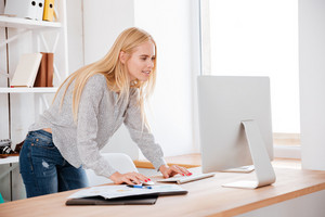 Smiling young business woman standing and looking on computer display at her workplace
