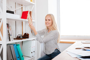 Smiling young business woman taking book from a shelf in office