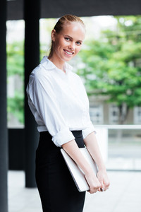 Smiling young business woman with laptop standong outdoors and looking at camera