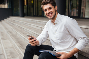 Smiling young businessman sitting and using mobile phone outdoors