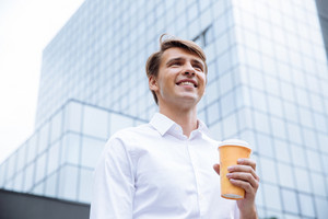 Smiling young businessman standing near business center and drinking coffee