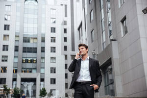 Smiling young businessman talking on mobile phone in the city
