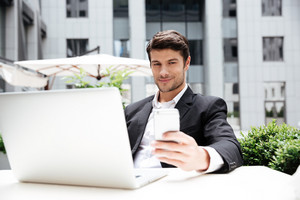 Smiling young businessman with laptop sitting and using mobile phone in outdoor cafe