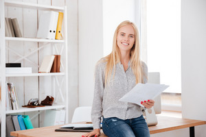Smiling young businesswoman holding documents and sitting on the office desk