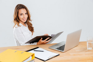 Smiling young businesswoman woking with documents and laptop over white background