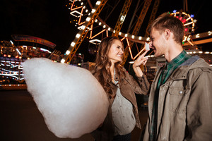 Smiling young couple eating cotton candy and having fun in amusement park