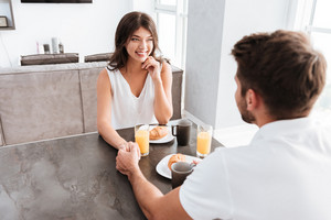 Smiling young couple having breakfast and holding hands at home