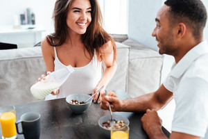 Smiling young couple having breakfast on the kitchen at home