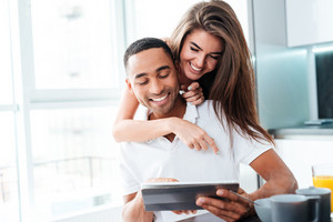 Smiling young couple hugging and using tablet on the kitchen