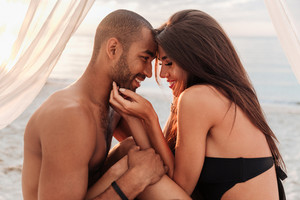 Smiling young couple hugging in bed on the beach