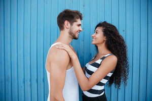 Smiling young couple in love standing and embracing over blue background