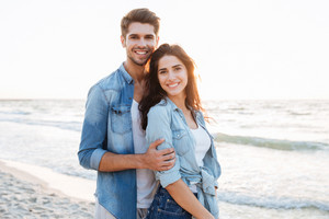 Smiling young couple in love standing at the beach