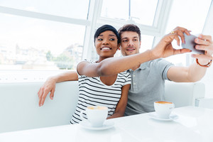 Smiling young couple making selfie photo on smartphone indoors in cafe