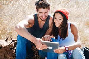 Smiling young couple on camping trip using digital tablet outside