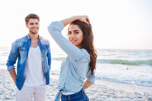 Smiling young couple standing and flirting on the beach
