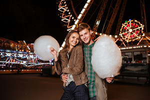 Smiling young couple with cotton candy. in amusement park. in warm clothes
