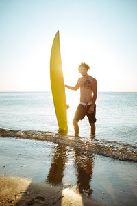 Smiling young curly man holding his surf board while standing in the ocean at the beach