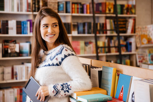 Smiling young female student holding a tablet computer in a library