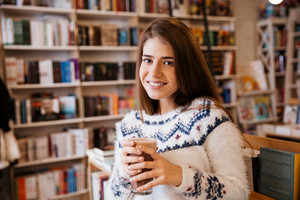 Smiling young girl in sweater with cup of coffee in library