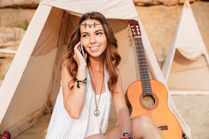 Smiling young hippie girl talking on mobile phone while sitting at the beach tent
