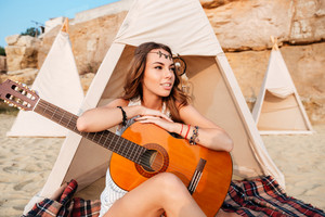Smiling young hippie woman posing with guitar at the beach tent